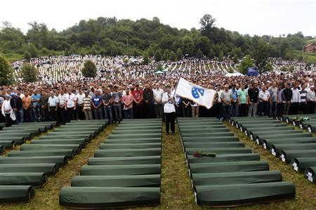 Bosnians pray in front of 409 coffins of newly identified victims of the 1995 Srebrenica massacre in the Potocari Memorial Center, near Srebrenica