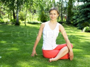 2328852-young-girl-in-a-white-shirt-and-red-pants-doing-yoga-outdoors